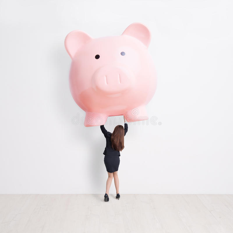 Business woman lift piggy bank. Business woman lift heavy pink piggy bank with white wall background, great for your design or text, asian stock photos