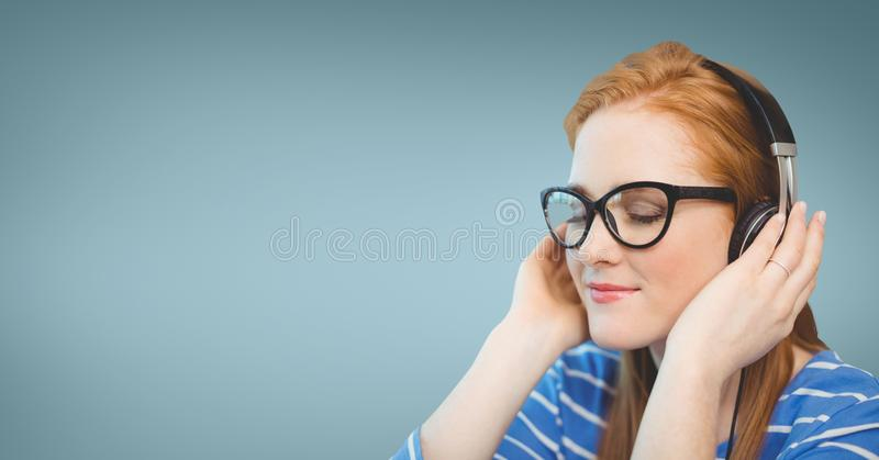 Business woman listening to music against blue background stock photo