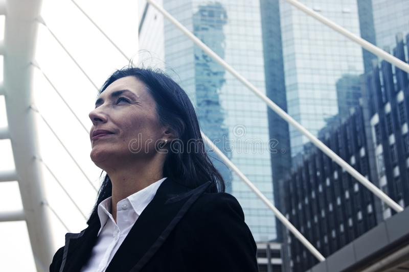 Business woman look up sky and offices building in the city. Business woman look up sky and offices building in the city background royalty free stock photo