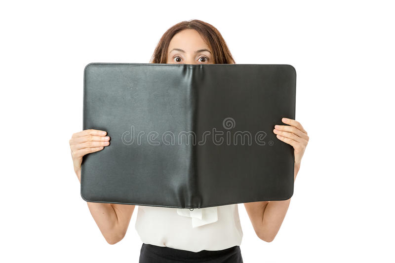 Business woman looking from behind a folder royalty free stock image
