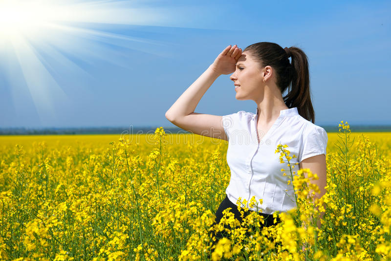 Business woman looking into the distance. Young girl in yellow flower field. Beautiful spring landscape, bright sunny day, rapesee royalty free stock images