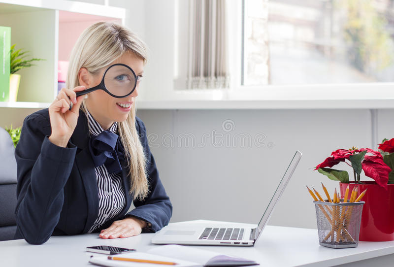 Business woman looking through a magnifying glass while sitting stock images