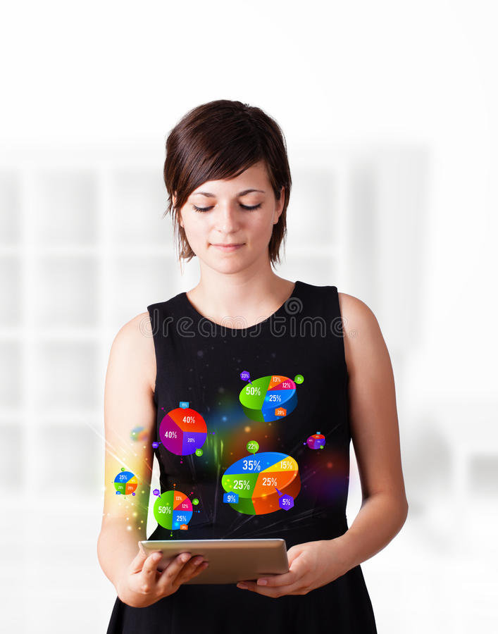 Business woman looking at tablet with pie charts. Young business woman looking at modern tablet with colourful pie charts royalty free stock images