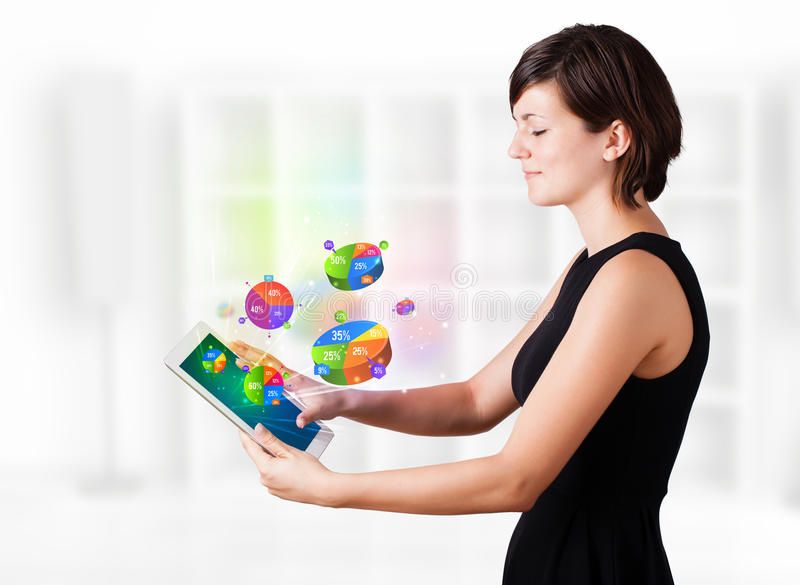 Business woman looking at tablet with pie charts stock image