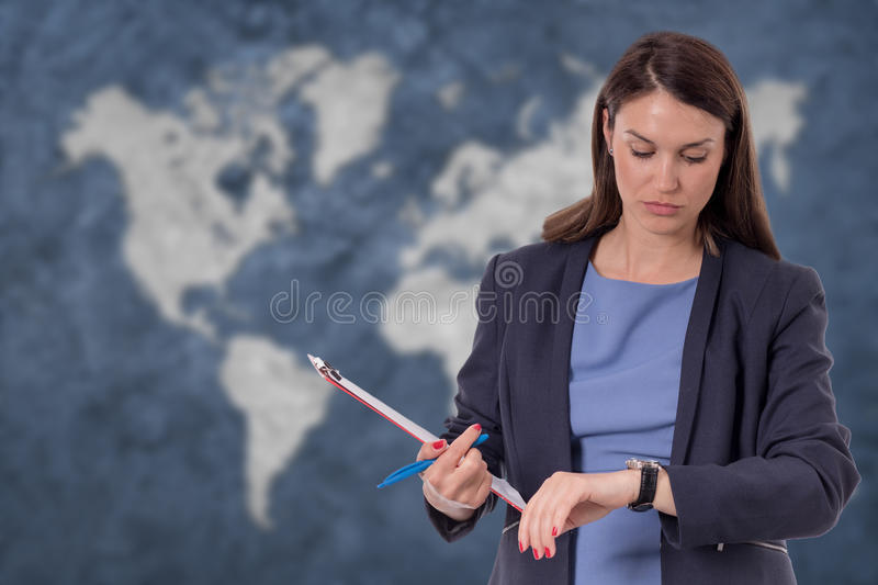 Business woman looking at watch. World map globalization concept stock images