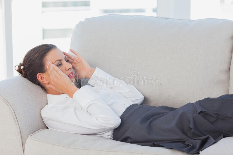 Business woman lying on couch with headache. In the office stock image