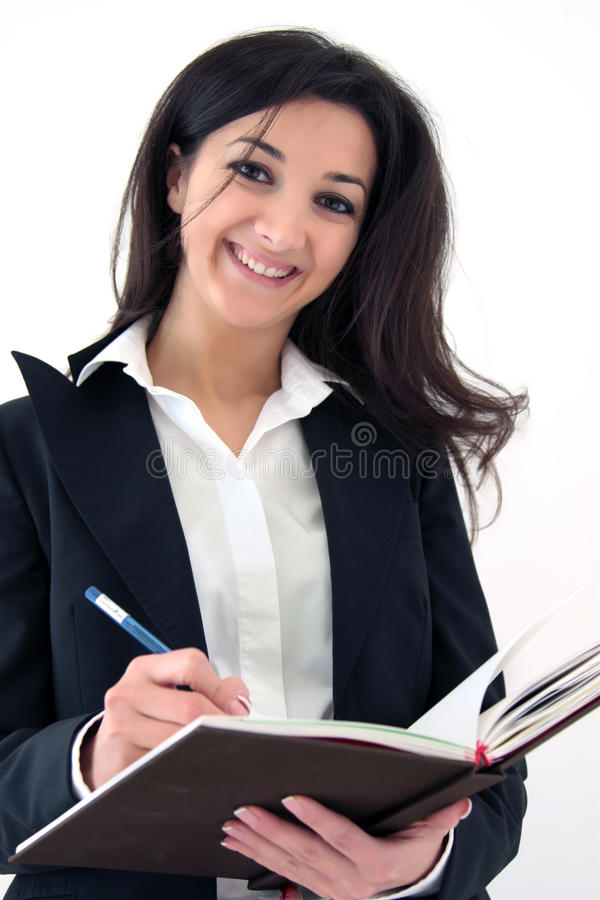 Business woman making notes. Portrait of young smiling business woman making notes in diary isolated over white background royalty free stock image