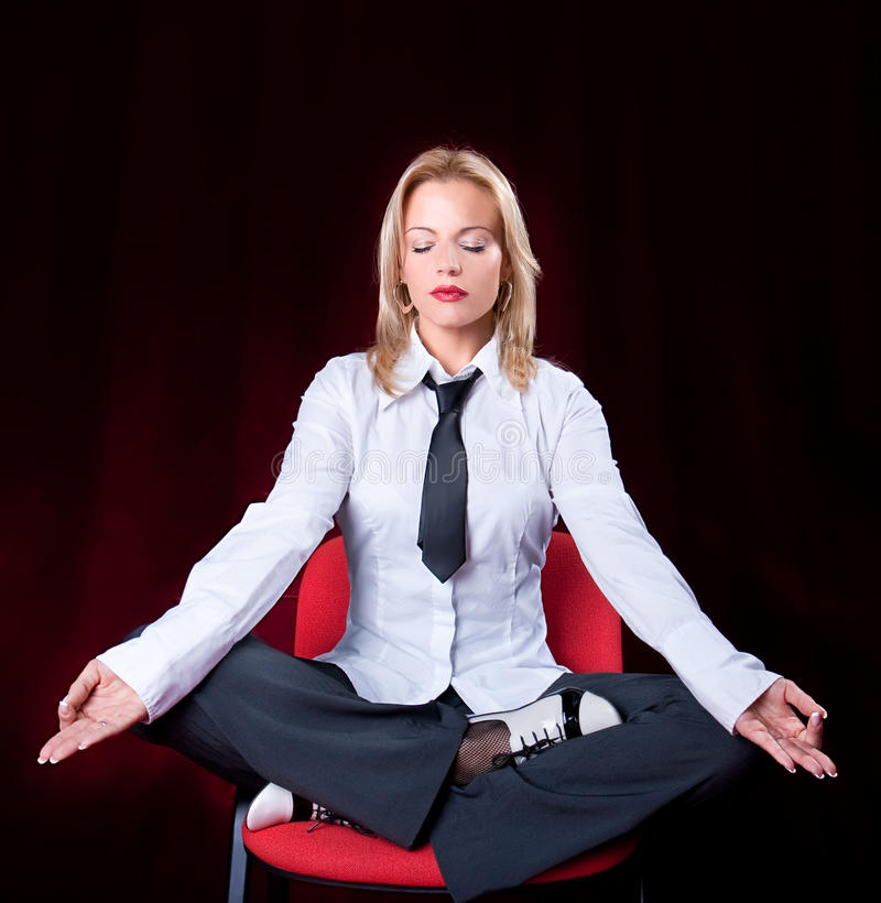 Business woman meditating. Portrait of business woman meditating on the chair in the office, red background stock photos