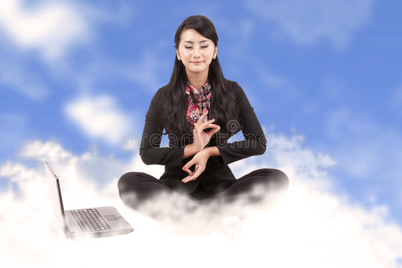 Business woman meditating above the clouds stock photography