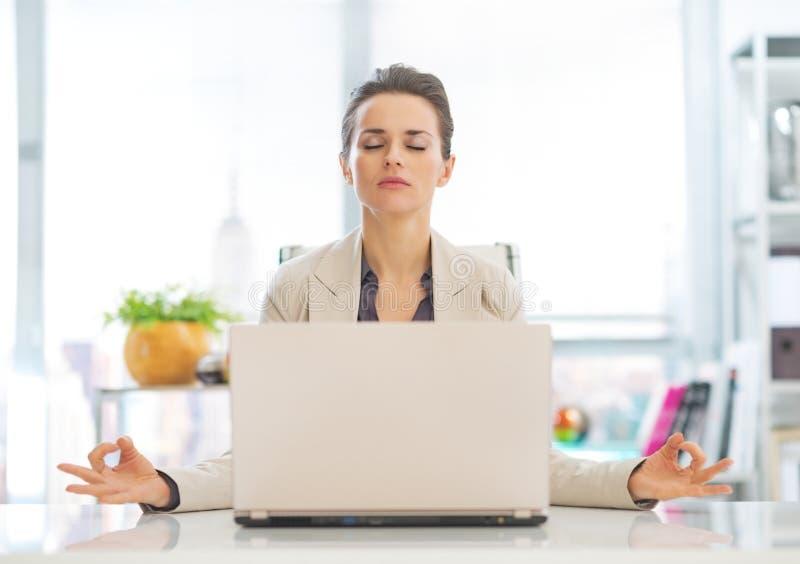 Business woman meditating near laptop stock photo
