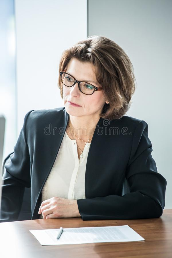 Business woman at meeting table. Mature business woman in flasses sitting at meeting table in office royalty free stock photo