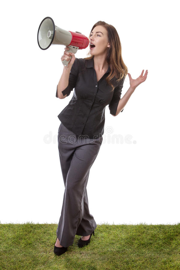 Business woman with megaphone. Pretty brunette holding a loud speaker in a business suit, standing on grass isolated on white royalty free stock image