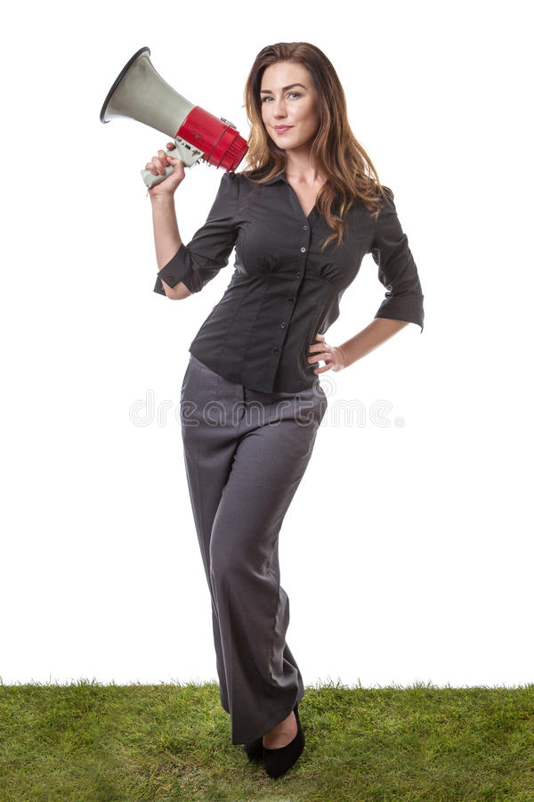 Business woman with megaphone. Pretty brunette holding a loud speaker in a business suit, standing on grass isolated on white stock images