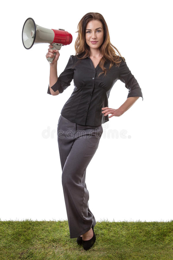 Business woman with megaphone. Pretty brunette holding a loud speaker in a business suit, standing on grass isolated on white royalty free stock images