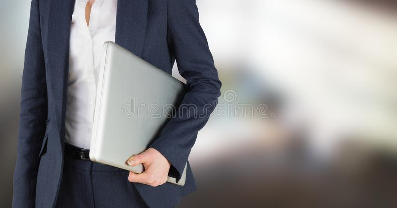 Business woman mid section holding laptop in blurry room. Digital composite of Business woman mid section holding laptop in blurry room stock photos
