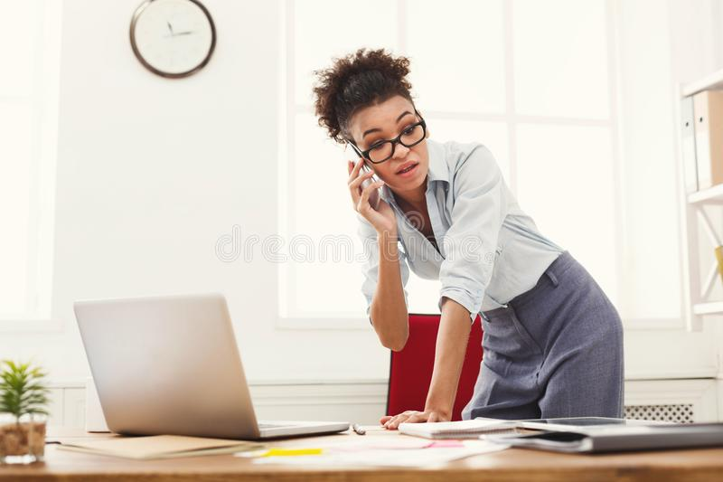 Business woman with mobile phone standing at office stock photography