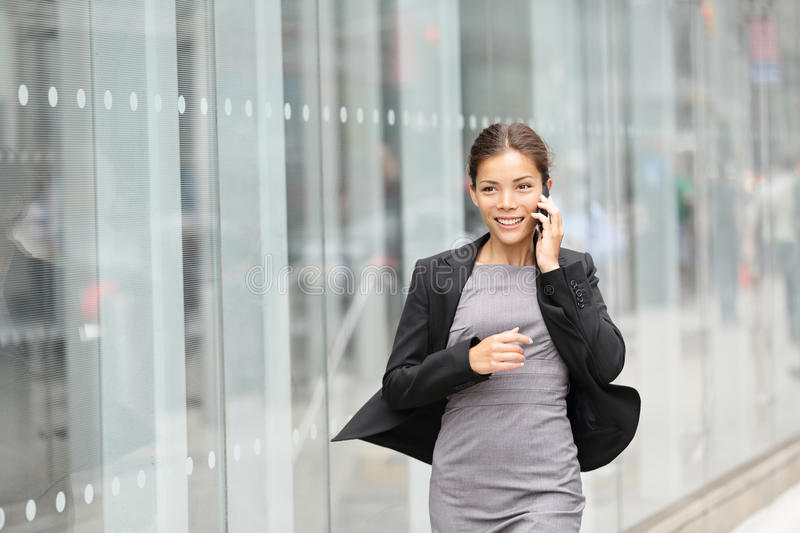 Business woman in motion. Talking on mobile smart phone running outside on Manhattan, New York City. Beautiful young professional businesswoman. Multiethnic stock photo