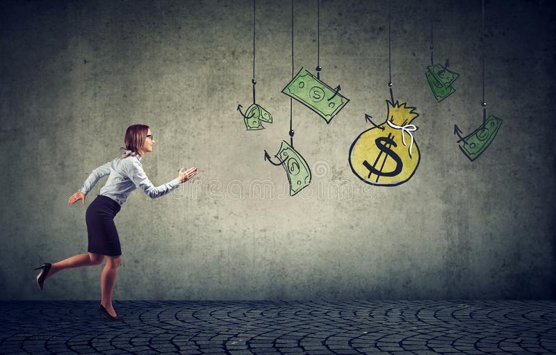 Business woman motivated by money hanging on a fishing hook. Businesswoman running for cash dollar royalty free stock photo