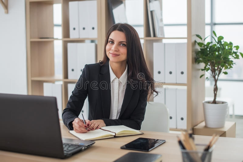 Business woman with notebook in office, workplace. Young business woman with notebook in the office, workplace royalty free stock photos