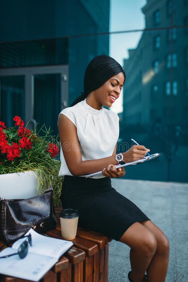 Business woman with notepad sitting on the bench royalty free stock photo