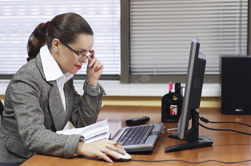 Business woman at office. The young business woman behind a workplace stock photos