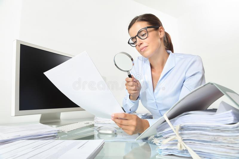 Business woman in office check documents and contracts with mag. Nifying glass sitting at the desk isolated on white background royalty free stock photo