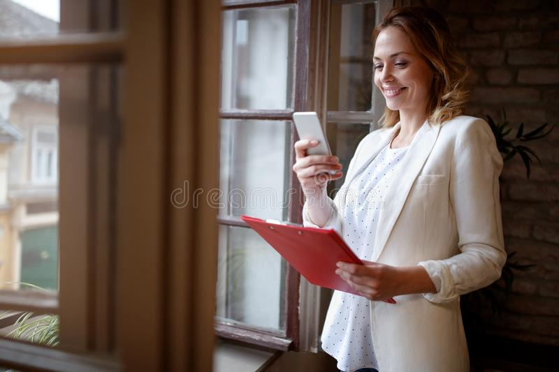 Business woman in office dialing with cell phone royalty free stock photos