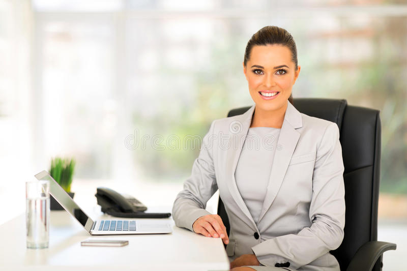 Business woman office. Happy young business woman sitting in office royalty free stock image