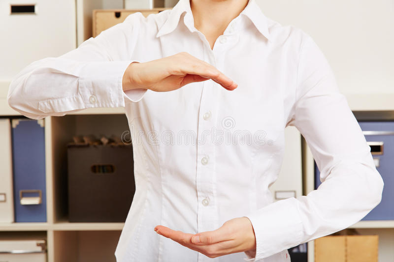 Business woman in office holding her hands open. Young business woman in office holding her hands open stock photography