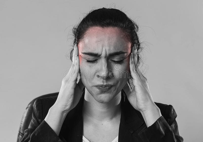 Business woman in office suit suffering migraine pain and strong headache. Black and white close up face of young business woman in office suit suffering royalty free stock photo