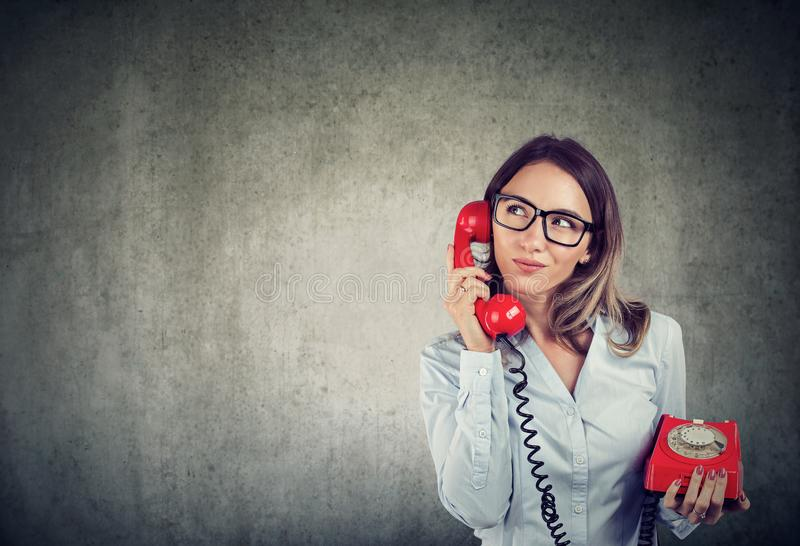 Business woman with an old fashioned tellephone carefully listening to a customer royalty free stock images