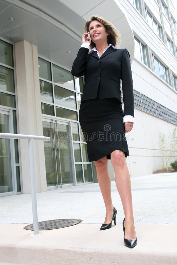 Business Woman Outdoors on Cell Phone. Business woman outdoors talking on cell phone, street view in front of a corporate office building royalty free stock photography