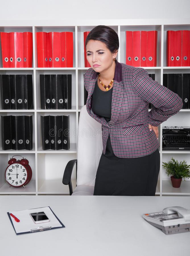 Business woman with pain in her back  in office stock photo