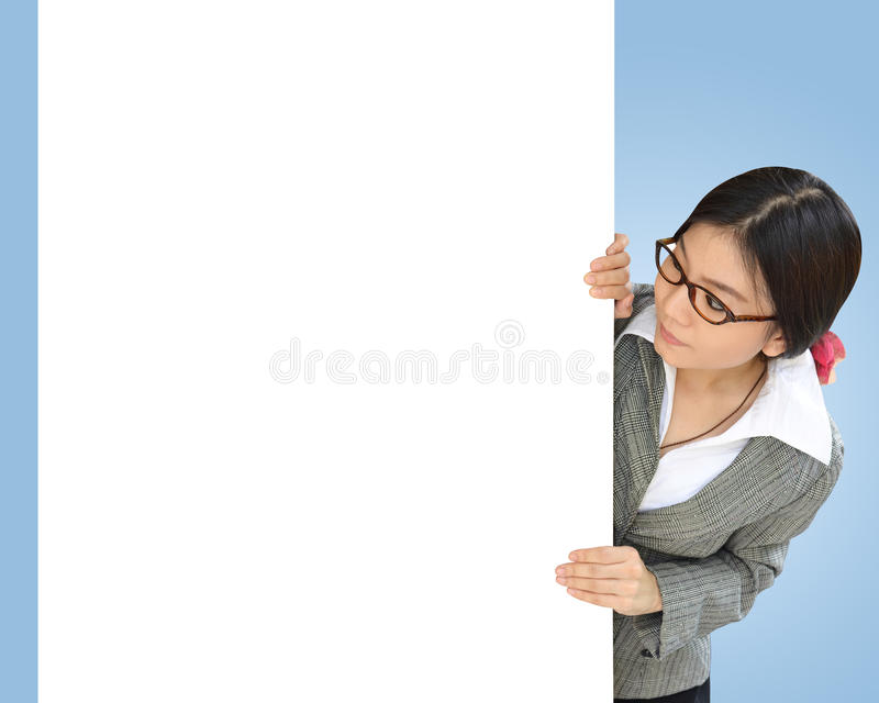 Business woman peeping over white billboard stock photo