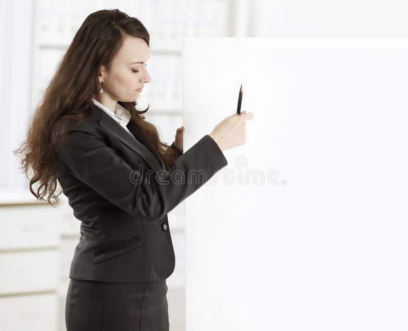 Business woman with a pencil pointing at a blank poster. Photo with copy space royalty free stock image