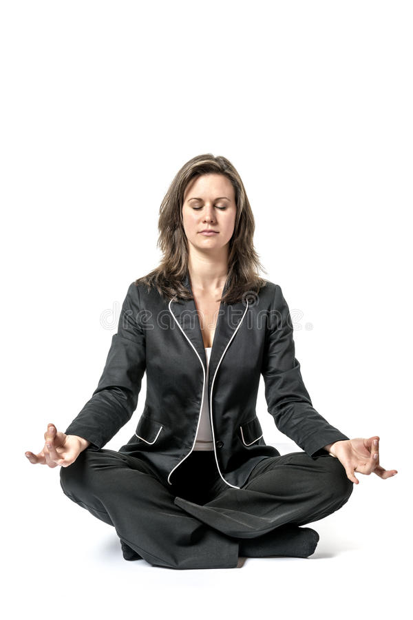 Business woman performs yoga. Business woman in black suit performs a yoga exercise on white background royalty free stock photography