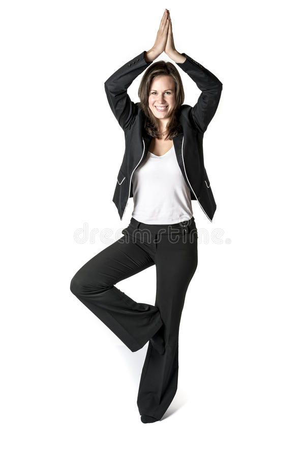 Business woman performs yoga. Business woman in black suit performs a yoga exercise on white background royalty free stock photo