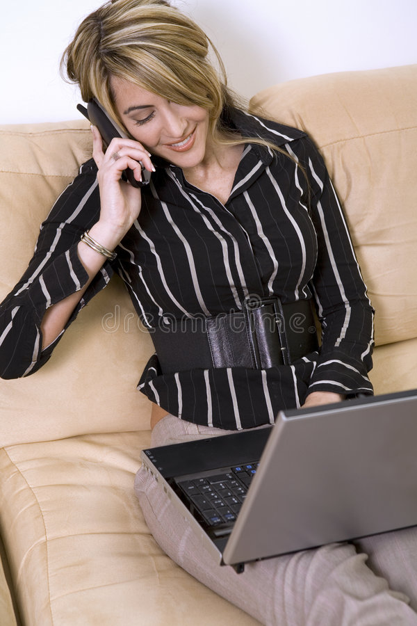 Business woman on the phone and laptop. Beautiful woman sitting on the sofa in living room wearing businesss wear and talking on the phone and using her laptop stock images