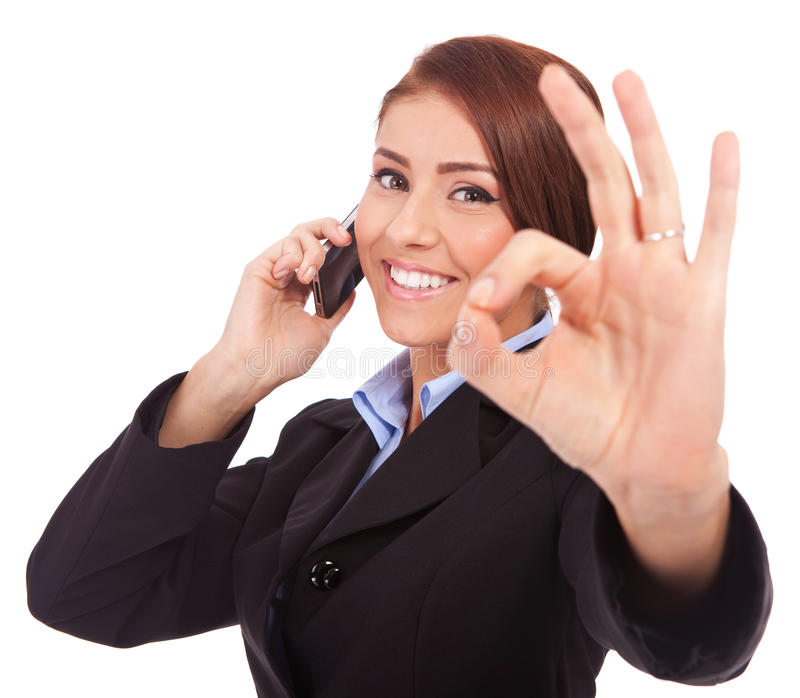 Business woman with phone and ok gesture. Happy business woman with phone and ok gesture, isolated royalty free stock images