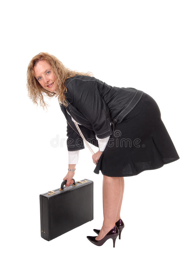 Business woman picking up her briefcase. A business woman bending down picking up her briefcase in high heels, looking into the camera, isolated for white stock photo