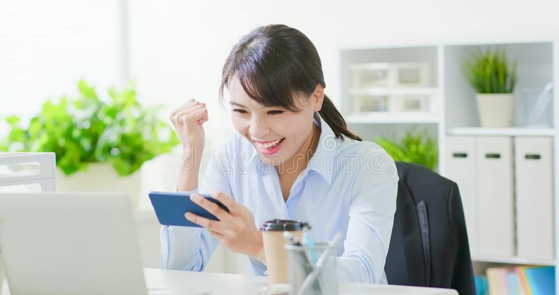 Business woman play mobile game. With a smart phone in the office royalty free stock images