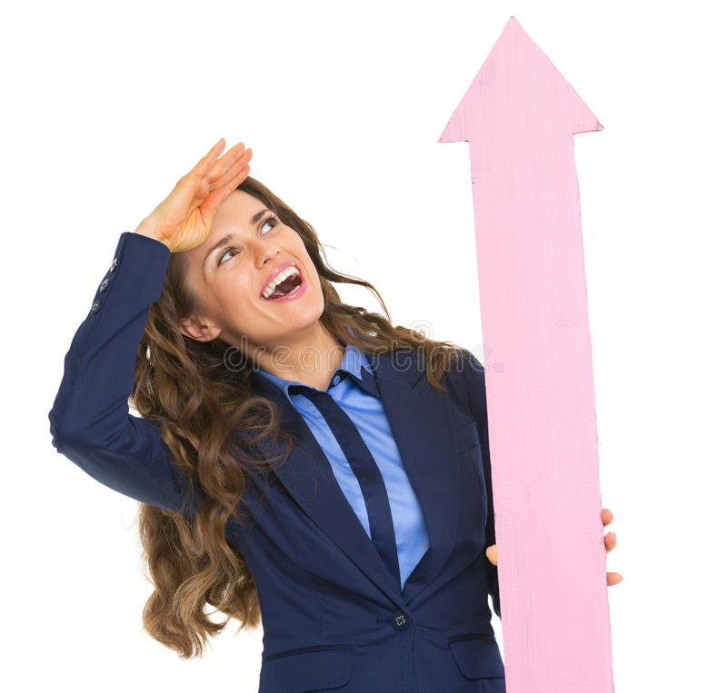 Business woman pointing with arrow up and looking into distance. Smiling business woman pointing with arrow up and looking into distance royalty free stock image