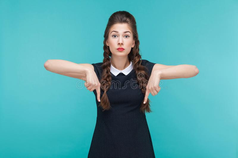 Business woman pointing finger down, at copy space. Studio shot, blue background royalty free stock photos