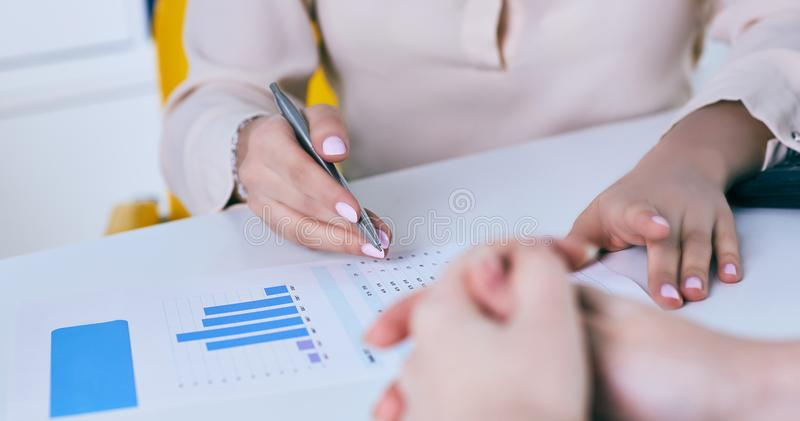 Business woman pointing at graph document close-up. royalty free stock image
