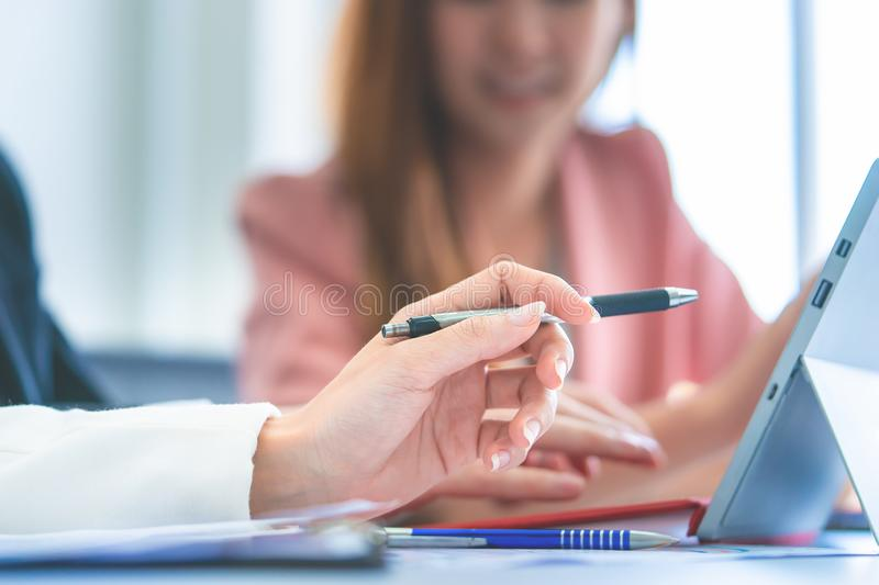 Business woman pointing on laptop screen, Coworker brainstorming in office computer stock photo