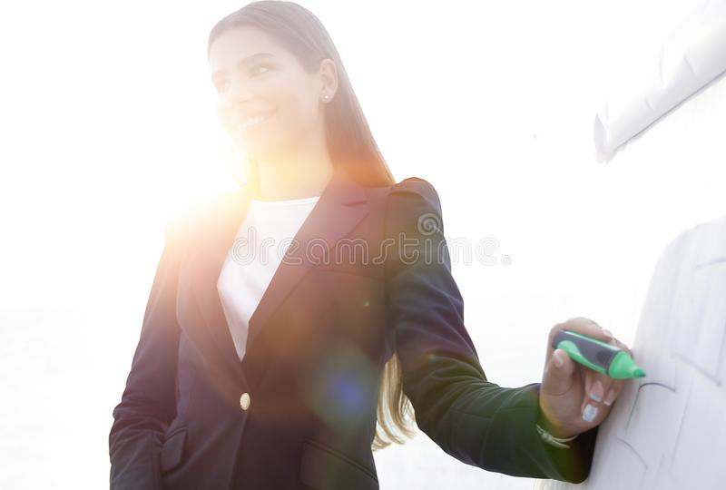 Business woman pointing with a marker on the flipchart royalty free stock photography