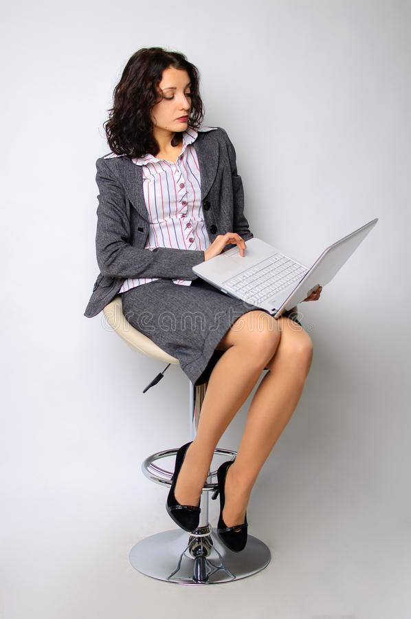 Business woman portrait. The brunette is walking on a high chair. He holds a a laptop. Isolated royalty free stock images