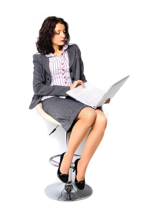 Business woman portrait. The brunette is walking on a high chair. He holds a a laptop. Isolated stock photography