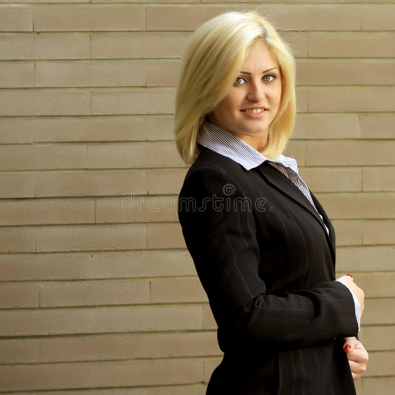 Business woman portrait next to a brick wall royalty free stock photos
