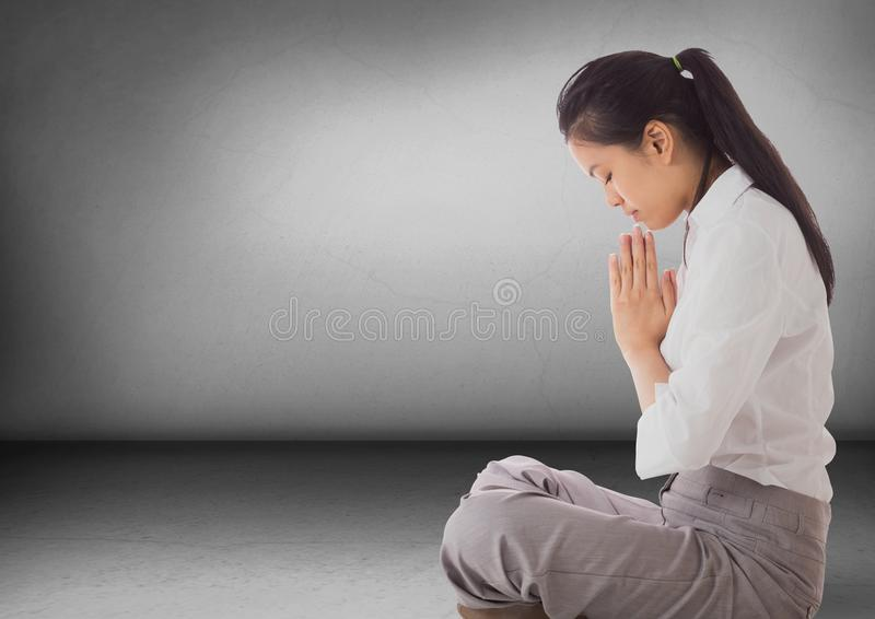 Business woman with praying in grey room. Digital composite of Business woman with praying in grey room royalty free stock photo